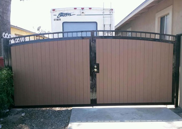 Vinyl fence with metal gate Diy Jj Fence Installed This Driveway Entry Gate In Torrance Ca It Is Double Swing Gate With Wood Grain Vinyl Boards And Features Brown Double Arched Lowes Jj Fence Vinyl Fence Gallery Vinyl Fence Installation Los Angeles
