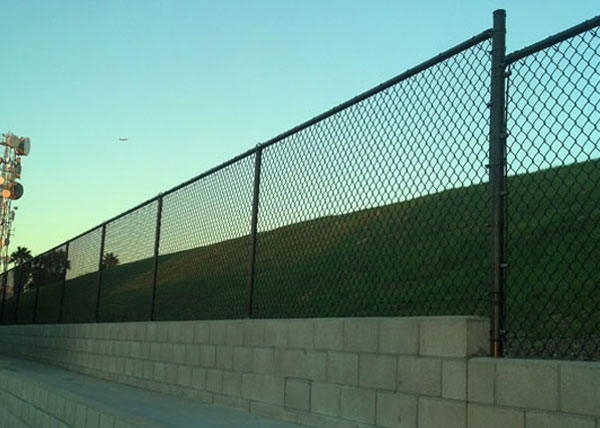 chain link fence post installation. The Black Vinyl Coated Commercial Chain Link Fence Is 5-feet Tall And Installed On Top Of A Block Wall. Posts Post Installation